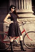 stock photo of bowler  - Beautiful brunette standing near her old bicycle over city background - JPG