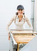 Portrait of happy young female beekeeper working in honey processing area