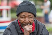 stock photo of homeless  - Portrait of homeless man thinking while sitting outdoors during the daytime - JPG
