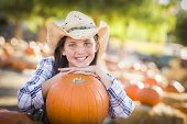 Portrait of Preteen Girl Wearing Cowboy Hat Playing at the Pumpkin Patch in a Rustic Country Setting.