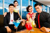 Young and handsome Asian Chinese people drinking cocktails in a luxurious and fancy lounge bar drinking cocktails