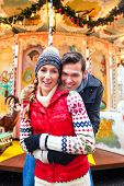 foto of merry-go-round  - Man and woman or  a couple  or friends during advent season or holiday in front of a carousel or merry - JPG