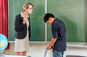 Teacher or educator criticize a pupil or student or boy in front of a blackboard in school