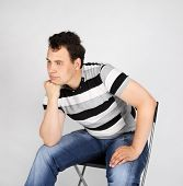 Brunet Man In Striped T-shirt Sits On Chair And Thinks On Grey Background.