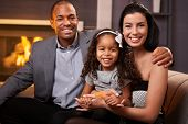 Portrait of beautiful mixed race family at home by fireplace, all smiling, little girl in the middle