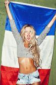stock photo of citizenship  - Young woman holding a french flag against a green wall background - JPG