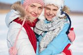 Happy woman and her son in winterwear looking at camera
