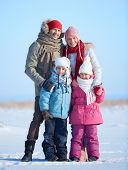 Happy parents and their kids in winterwear looking at camera outside