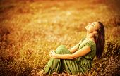Romantic woman wearing long elegant dress sitting on golden dry field, autumn season, relaxation in
