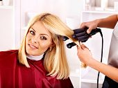 foto of hair curlers  - Woman at hairdresser with iron hair curler - JPG