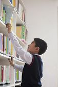 Schoolboy reaching for book off bookshelf
