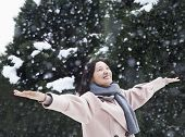 Woman with arms outstretched feeling the snow