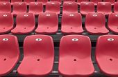 stock photo of grandstand  - Empty plastic chairs of red color are on grandstand stadium - JPG
