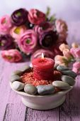 Composition with spa stones, candle  and flowers on color wooden table, on light background