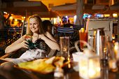pic of vivacious  - Smiling vivacious beautiful young woman sitting drinking at a counter in a cafeteria or pub in an indoor illuminated mall - JPG