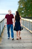 Young Interracial Couple Walking Together On Wooden Pier Over Lake