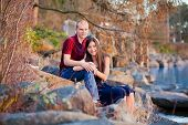 Young Interracial Couple Sitting Together On Rocky Shoreline By Lake