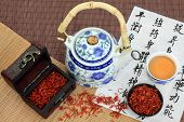 Safflower tea with teapot and cup and chinese calligraphy script which describes chinese herbal medi