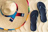 Straw Sombrero And Sandals On Beach Sand