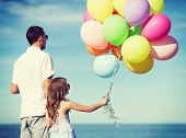 summer holidays, celebration, children and family concept - father and daughter with colorful balloo