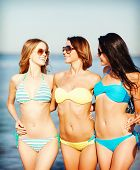 summer holidays and vacation concept - girls in bikinis walking on the beach