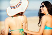 summer holidays and vacation - girls applying sun protection cream on the beach