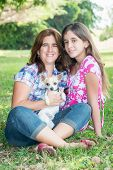 Young hispanic woman, her teenage daughter and their small chihuahua dog at a park
