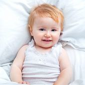 cute baby lying in a bed and smiling
