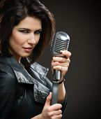 Portrait of female rock musician wearing black jacket and keeping microphone on grey background. Con