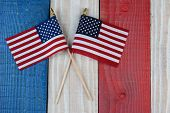Two American Flags on a red, white and blue painted wood surface. Perfect for Fourth of July or Memo