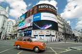 LONDON, ENGLAND - MAY 27,2013: a red cab taxi crosses the iconic video advertising billboards of Pic