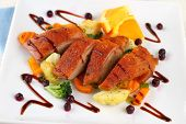 stock photo of duck breast  - Roasted duck breast vegetables wild blueberries close up - JPG