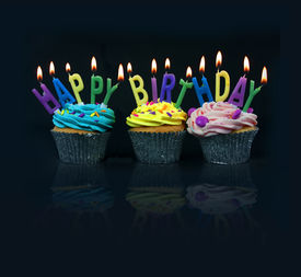 picture of happy birthday  - cupcakes spelling out happy birthday on a black background with reflection - JPG