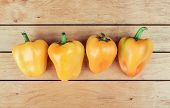 Four Yellow Bell Peppers On Table