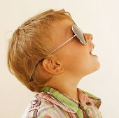 Little boy in sunglasses against white background