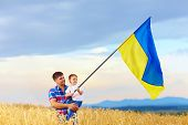 Father And Son Waving Ukrainian Flag On Wheat Field