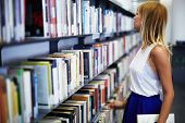 attractive female student standing near bookshelf looking for some book