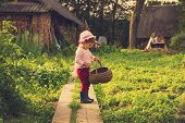 Cute kid with big basket having fun at countryside