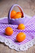 pic of kumquat  - Ripe fruit kumquat orange lying on a wooden surface against the background of purple basket - JPG