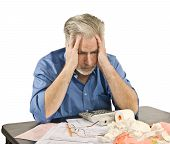stock photo of irs  - Mature man getting a headache from taxes and bills - JPG