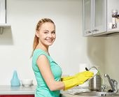 people, housework and housekeeping concept - happy woman in protective gloves washing dishes at home kitchen