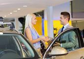 auto business, car sale, consumerism, gesture and people concept - happy woman with car dealer making deal and shaking hands in auto show or salon