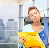 people, business and paperwork concept - young businesswoman with folders sitting on chair over office window background