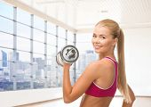 people, fitness and sport concept - close up of happy young woman flexing her biceps over gym or home background