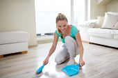 people, housework and housekeeping concept - happy woman with brush and dustpan floor at home