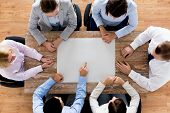 business, people and team work concept - close up of creative team sitting at table and pointing finger to blank paper in office