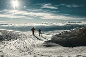Two skiers on the peak of mountain in sunny day. unfocused