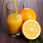 fresh orange juice pouring into glass on the table
