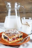 Homemade pie with jam and glass and jug of milk on white tablecloth and wooden planks background