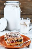 Homemade pie with jam and glass and can of milk on tablecloth and wooden background